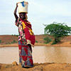 Photo of a woman with a jug of water on her head.