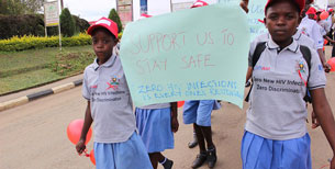 Two girls carry a sign saying Support Us to Stay Safe. Zero HIV Infections is everyone's responsibility.