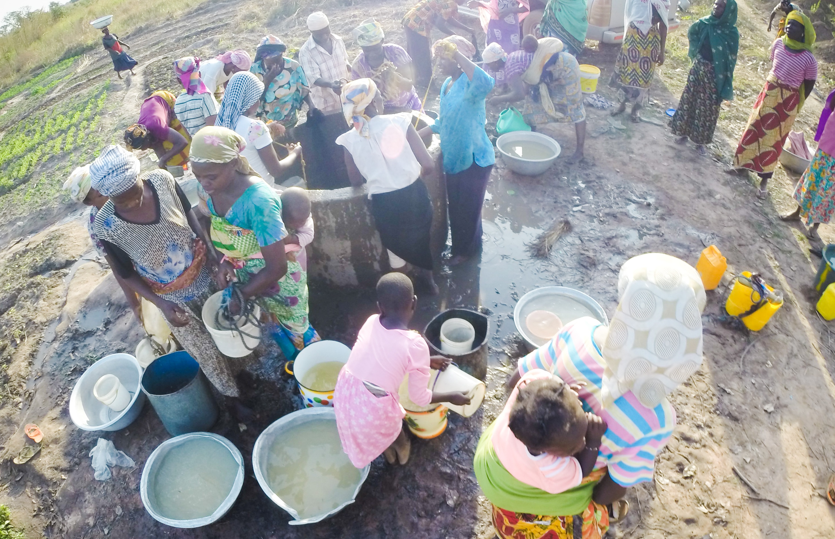 Women work together to collect water from a well for their community in northern Ghana.