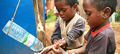 Two children wash their hands from a tipping water bottle
