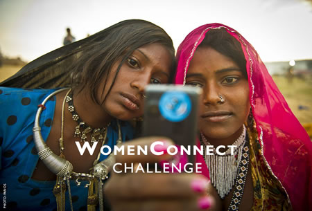 Photo of two young women using a cell phone. Photo credit: PANOS