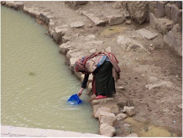 A Yemeni woman collects water from a USAID-funded cistern.