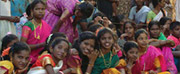 Photo of young girls in India watching a play about adult being encouraged to get tested for HIV.