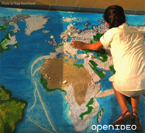 Open IDEO - A woman kneels on a map of the world