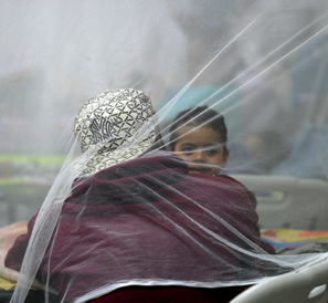 A mother and child beneath a protective mosquito net'
