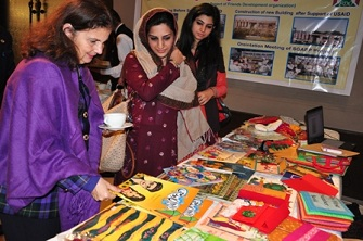 U.S. Consul General Nina Fite browsing through various education material on Alif Laila Book Bus Society stall at the USAID Educ