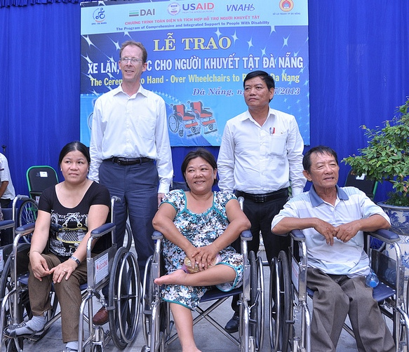 USAID Mission Director Joakim Parker, second from left, helps hand over wheelchairs to people with disabilities in Danang.