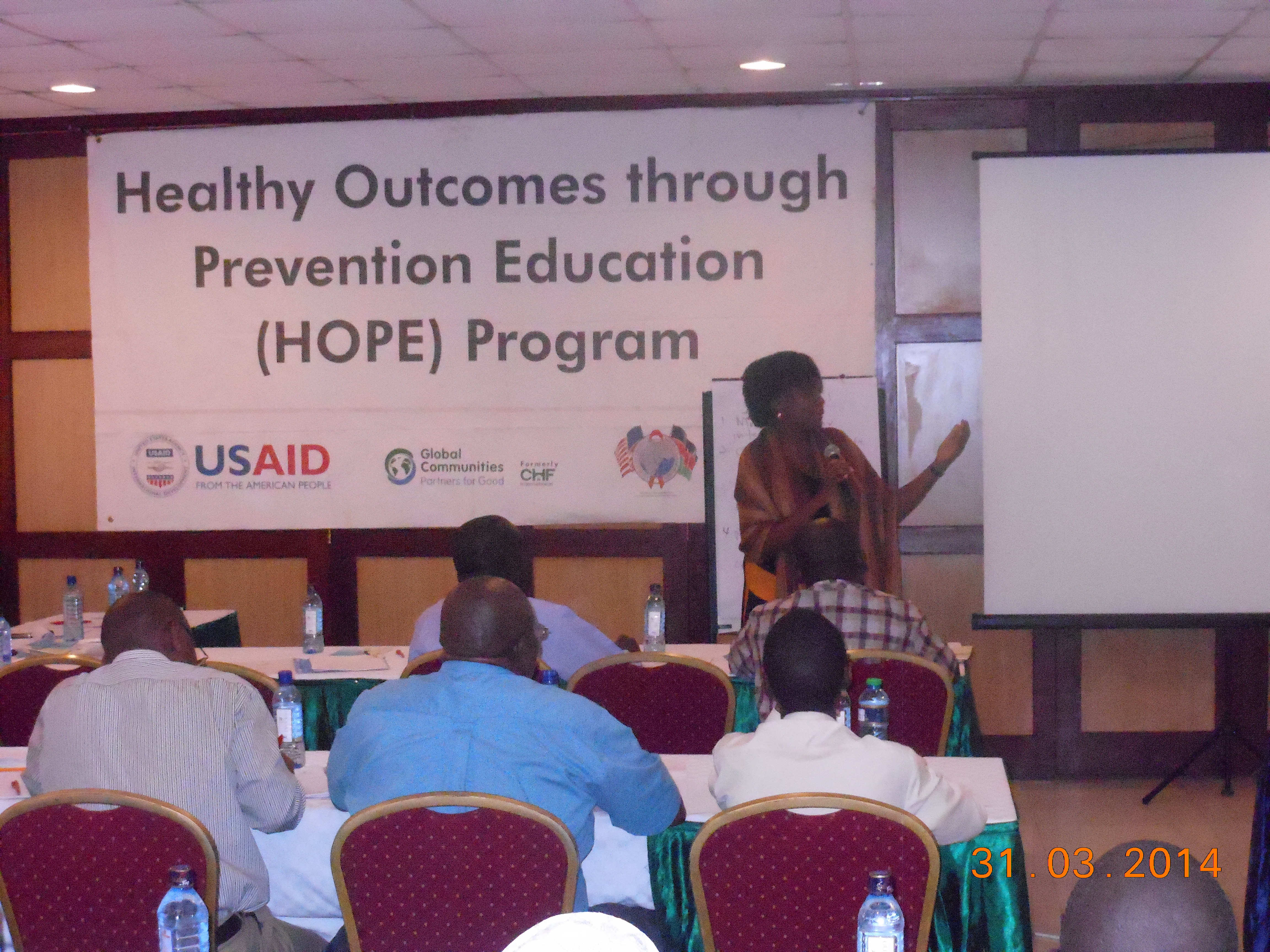 A Kenyan woman addresses an audience while standing in front of a banner that reads Health Outcomes Through Prevention Education