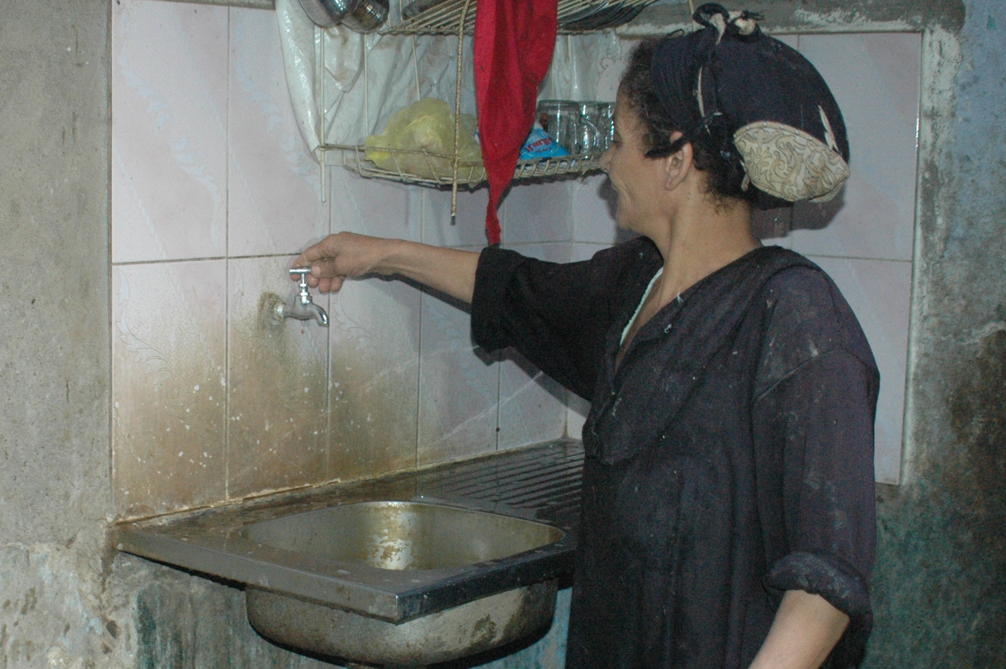Woman turns on water faucet in her home