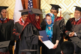 "Acting USAID Mission Director Carolyn ""Teddy"" Bryan awards a diploma for a new Master's degree graduate"