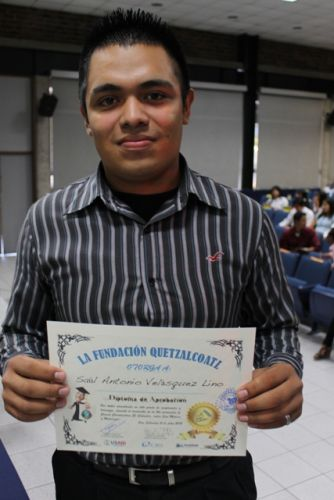 A young man poses with his new certificate
