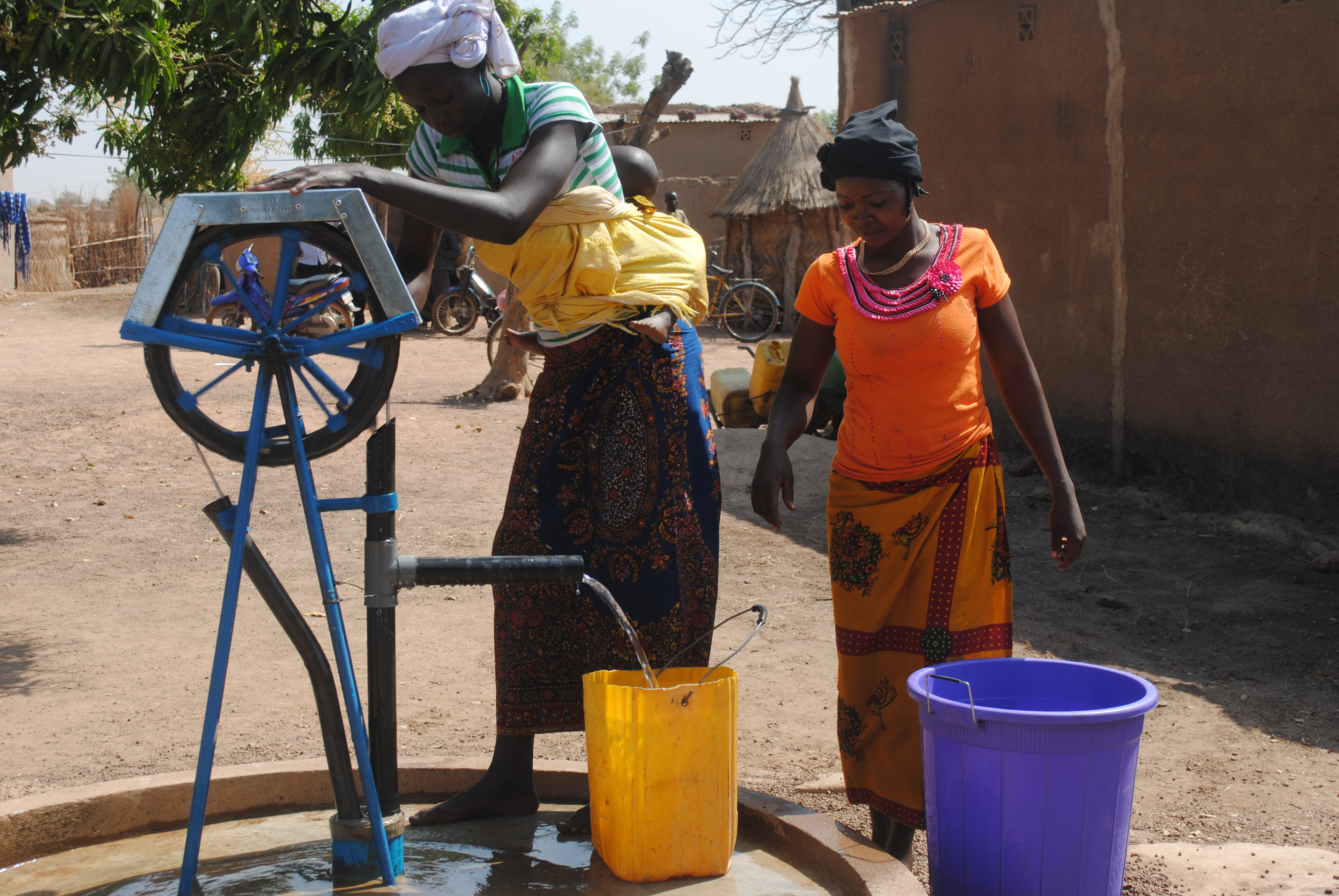 Women gathering water from a well improved by the USAID West Africa Water Supply, Sanitation and Hygiene Program