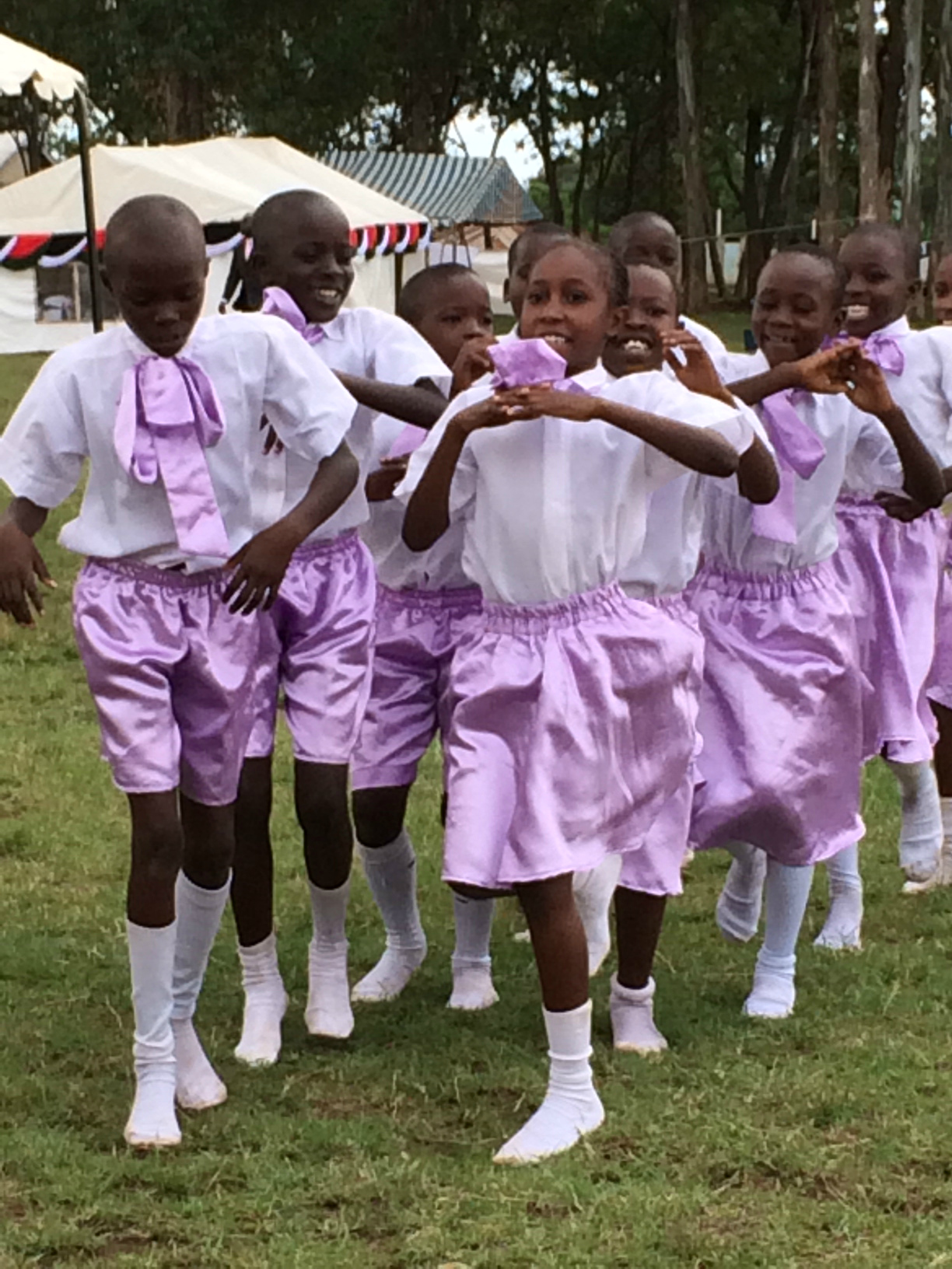 Two lines of Kenyan children wearing purple shorts march across a field