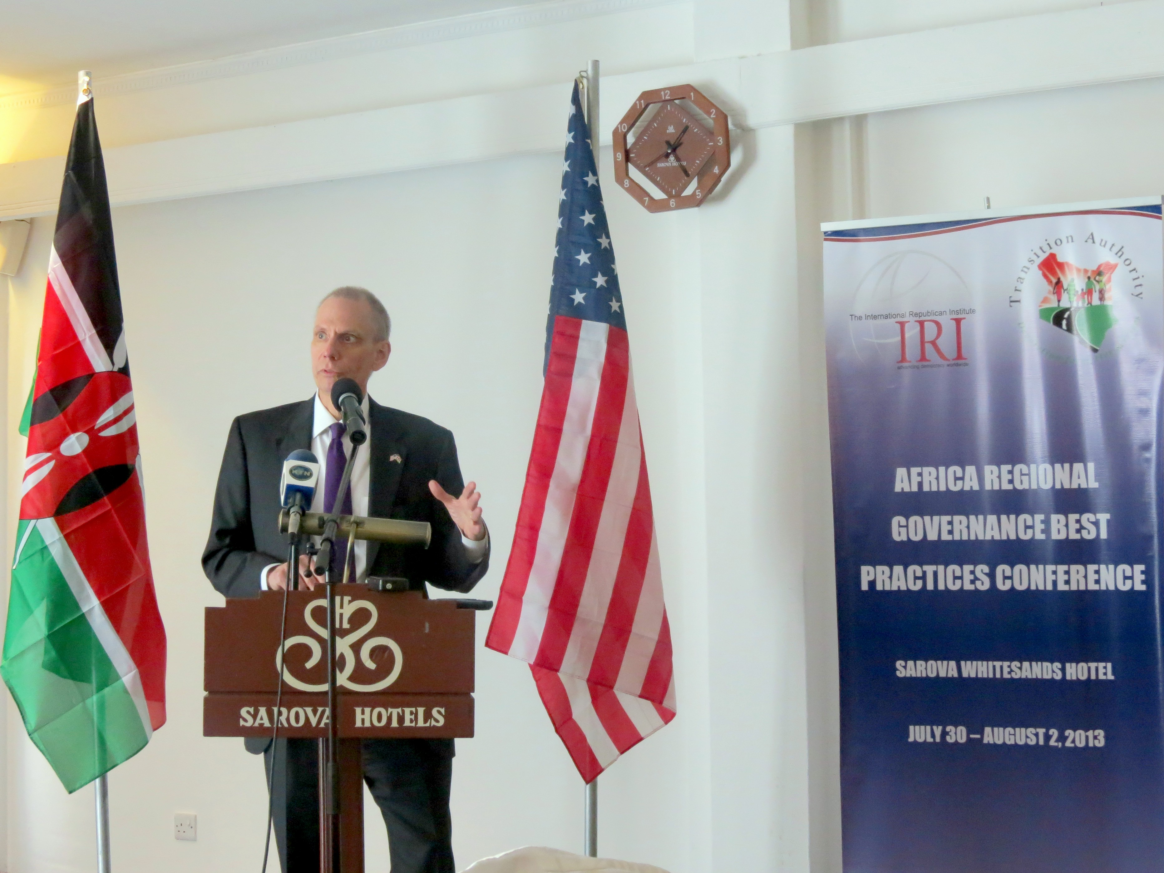 US Ambassador to Kenya speaks behind a podium flanked by Kenyan and American flags