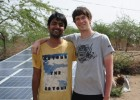 Yashraj Khaitan (left) and Jacob Dickinson, both founders of Gram Power, stand next to several solar panels in India. The panels