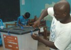A polling station worker opens the ballot box prior to counting votes. Independent observers concluded that the 2011 elections w