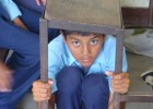 A student from Shree Janaudaya Lower Secondary School in Kathmandu, Nepal, demonstrates how to take cover during an earthquake.