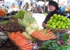 A woman sells vegetables at a local produce market in Georgia.