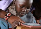 An iRead student at a primary school in Ghana gets to know his new Kindle and the dozens of books that come with it.