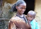 "A mother holds her child at their ""model home"" in a village outside Enticho Tigray, Ethiopia, served by the Endamariam Health Po"