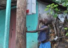 A Haitian boy inspects the installation of an early-stage microgrid meter box.