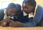 Kenyan students play a mobile game.