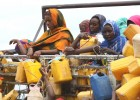 Ethiopian women grab containers with filled with fresh water