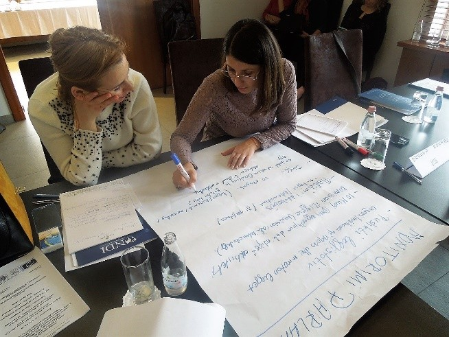 Two women write on a white poster board