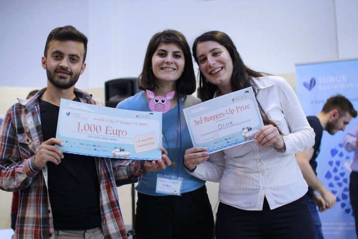 Two young women and a young man hold competition prize certificates for 1,000 euro