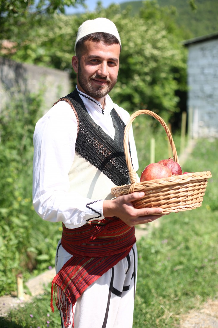 A young man dressed in traditional clothes holds a basket of pomegranites