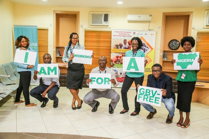 USAID staff in Nigeria hold up signs saying they are working for a GBV-free country.