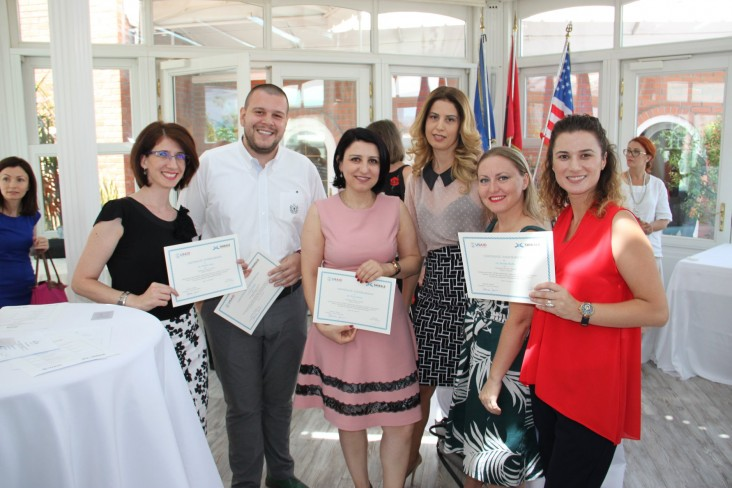 Young adults pose with USAID certificates
