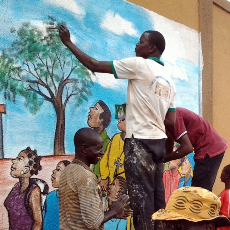 A group of youth in Burkina Faso painting a mural in their community