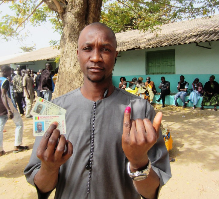 Senegalese holding his ID and voter's card after casting his vote in the 2012 presidential elections