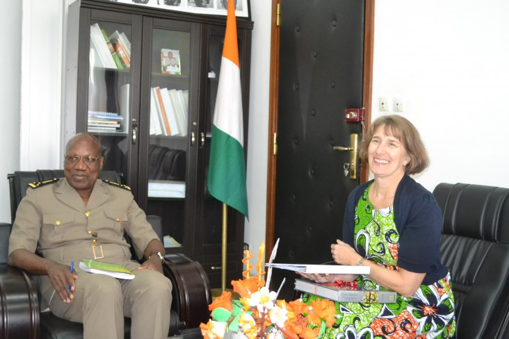 A Prefet is seating smiling next to the Ivoirian flag. U.S. Chargé d'Affaires Katherine Brucker seating accross him smiles.