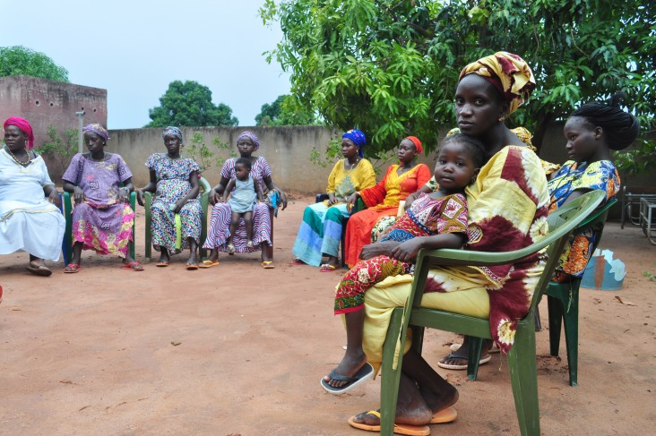Women and children gather at a community health group meeting