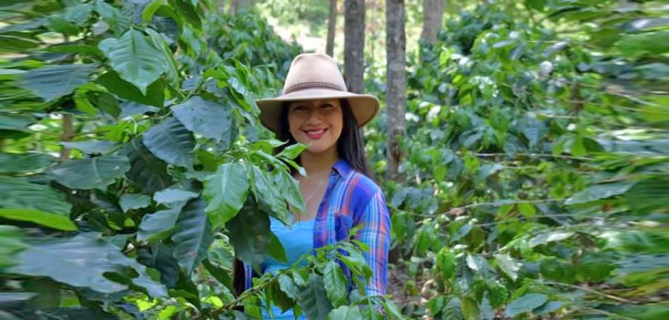 A smiling young woman stands among leafy green trees.