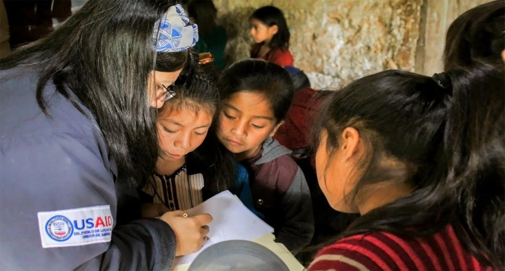 A woman from USAID asks children questions for a health survey