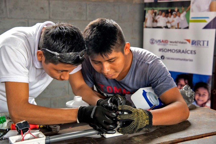 Two young men work on electrical components