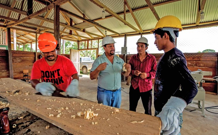 A supervisor provides direction to workers in a carpentry shop