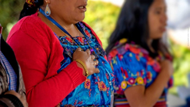 Close-up of indigenous women holding their right hand over their hearts