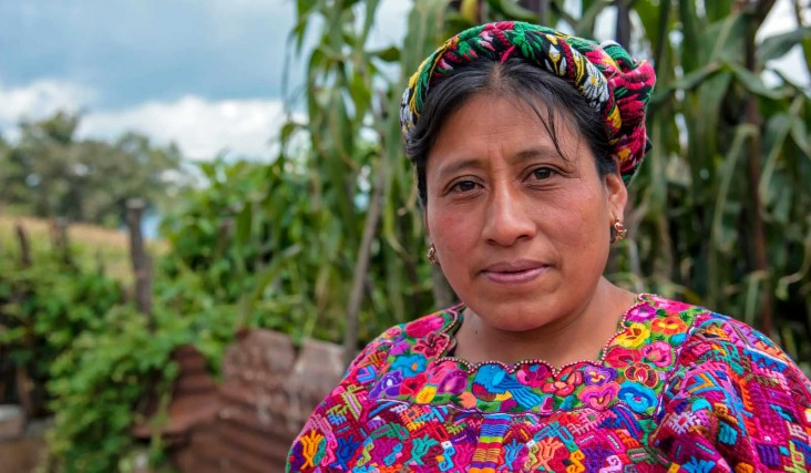 Close-up of an indigenous Guatemalan woman standing in natural setting with green trees and foliage behind her.