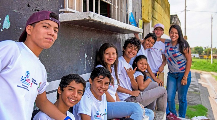 A row of smiling Guatemalan youths in USAID T-shirts
