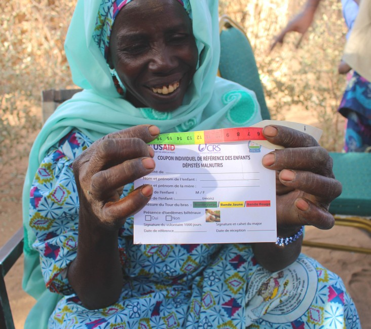 A woman shows off a baby weighing card in Niger