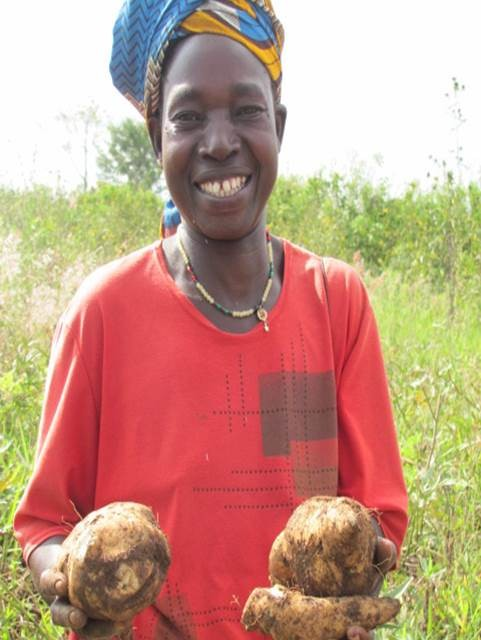 A woman farmer in East Africa shows her food crops.