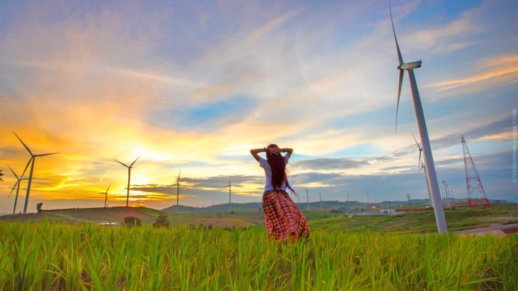 Happy woman relaxing with wind generators turbines beautiful sunset background.