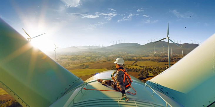 An engineer rests atop a large wind turbine admiring his work and the beautiful sunset landscape.