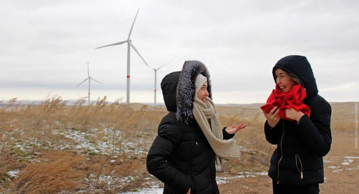 Two happy women in winter clothes chat in a dry amber field with wind turbines in the distance set against a gray sky