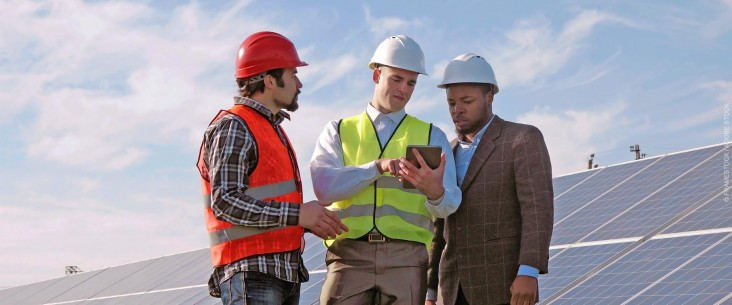 Three engineers examine data on a tablet in front of a large photovoltaic array