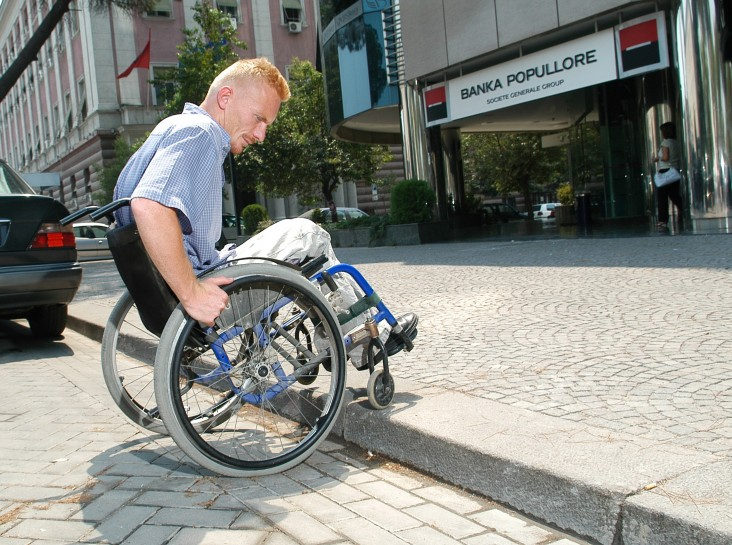 A young man in a wheelchair accessing a sidewalk without a wheelchair ramp